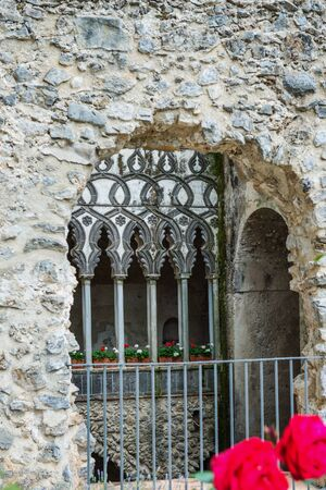 planters: View through historic rock portal over railing on corridor old Italy with red flowers in the foreground and in planters far away Stock Photo