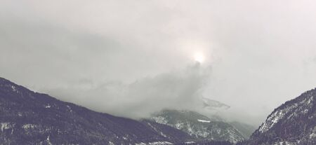 peaking: Panoramic view of light from sun barely peaking from clouds above beautiful tall mountain range