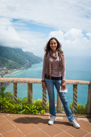 Young attractive Indian female tourist standing on an open-air balcony overlooking the Amalfi coast, Italy smiling at the camera Stock Photo