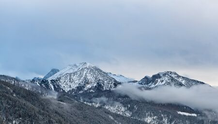 foothills: View of Alps mountain peaks and slow moving thick clouds around them with foothills in foreground during winter season