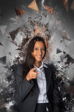 woman business suit: Single happy young professional woman in business suit pointing finger ahead while surrounded by powerful exploding glass ceiling concept