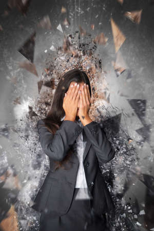 shielding: Businesswoman shielding her eyes from an explosion as shards of shattered building fly past her at speed in a conceptual image
