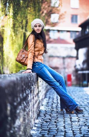 full willow: Full Length Portrait of Attractive Young Indian Girl Wearing Leather Jacket and Cap Sitting on Wall of Urban Cobblestone Bridge with Willow Trees