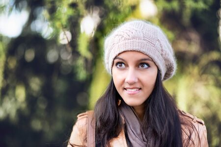 Head and Shoulders Portrait of Attractive Young Indian Girl Wearing Leather Jacket and Wool Cap Smiling and Looking to the Side in Outdoor Setting with Willow Trees in Background Stock Photo