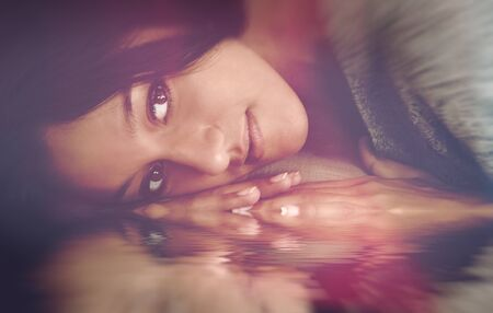 introspective: Evocative portrait of a pensive young woman lying down with her face and hands reflected in water and a serene expression Stock Photo