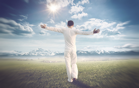 eternal: Man dressed in white celebrating the beauty of nature walking with open arms across a grassy field towards distant snow-covered mountains, toned and vignette Stock Photo