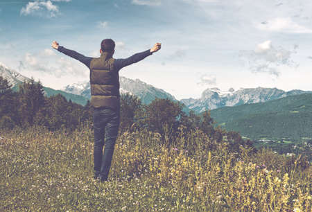 outstretched arms: Man celebrating the freedom of the mountains standing on a grassy plateau with outstretched arms facing distant mountain peaks Stock Photo
