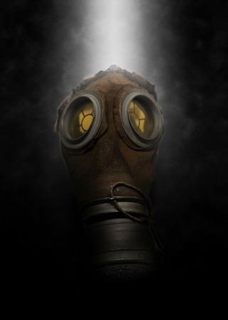 pollutants: Single poisonous gas mask for soldier with with spray of mist behind it over dark gloomy background