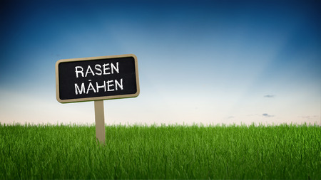 lawn mowing: German language lawn mowing text in white chalk on blackboard sign in flowing green turf grass under clear blue sky background