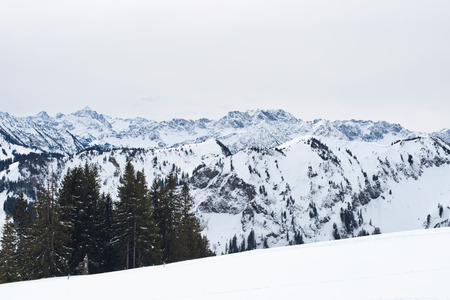 bleak: Panoramic vista of snow covered mountains and valleys stretching away into the distance viewed from a snowy summit on a cold bleak winter day