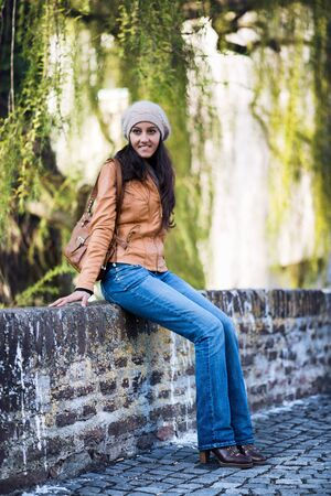 Full Length Portrait of Attractive Young Indian Girl Wearing Leather Jacket and Cap Smiling and Sitting on Wall of Cobblestone Bridge with Willow Trees in Background
