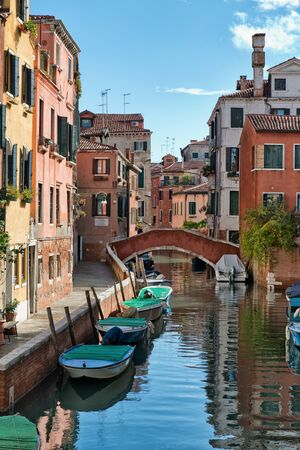 Street scene with a water canal, moored boats and historic buildings in Venice, Italy Editorial