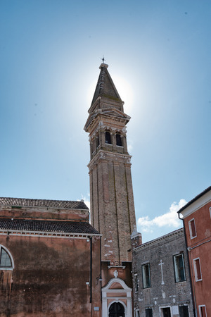 martino: Backlit view against bright sunshine of the leaning campanile tower of San Martino Church on the island of Burano, Venice, Italy
