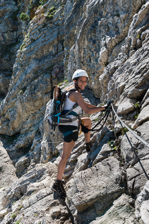 mountaineer: Smiling fit young female mountaineer standing on a steep rocky slope holding onto ropes turning to smile at the camera Stock Photo