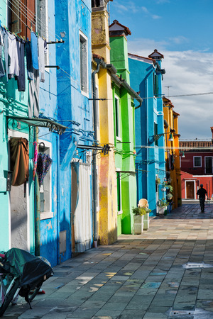 row of houses: Architectural Exterior of Brightly Colored Row Houses on Sunny Day on Burano, Islands of Murano, Venice, Italy Stock Photo