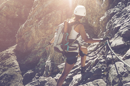 Lone female hiker with backpack, white helmet and safety rope, ascending while turning to look toward rocks with copy space