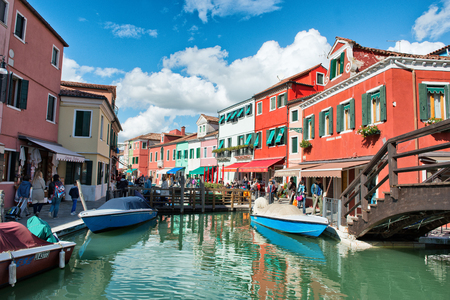 sightseers: Canal scene on Burano, Venice, Italy with moored boats below a wooden bridge, colorful buildings and crowds of tourists and sightseers