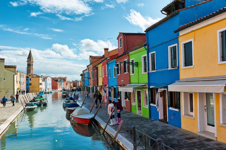 islanders: Tourists and islanders walking along a canal, Burano, Venice, Italy lined with brightly colored houses for which the island is famous