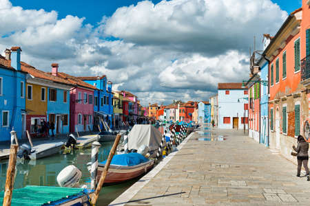 Woman walking along a canal on Burano, Venice, Italy past moored boats on the water and brightly colored fishermen houses in a travel and tourism concept