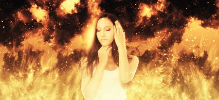conflagration: Young woman standing in front of a blazing inferno with a serene expression and eyes closed in meditation, wide angle panoramic banner