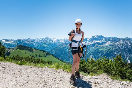 Single pretty young woman in hiking outfit exploring in the mountains under clear sky Stock Photo - 60637789
