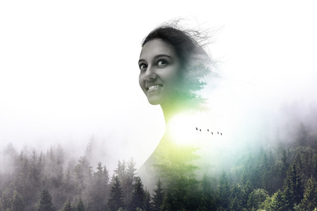 Ghostly appearance double exposure portrait of smiling beautiful young woman above evergreen forest trees with copy space