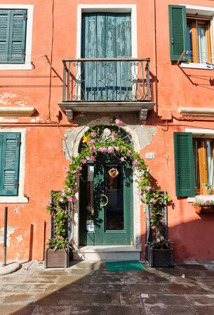 entrance arbor: Pretty rose arbor with fresh pink flowers over an entrance door to a house on Burano, Venice, Italy with its brightly colored facade Editorial