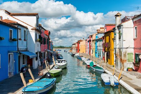 glimpse: Peaceful colorful canal scene, Burano, Venice with boats moored along the canal in front of brightly colored houses and a glimpse of the lagoon in the background Editorial