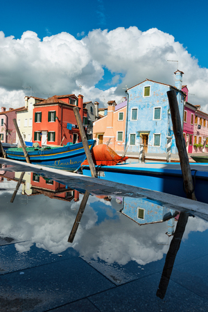 alongside: Colorful houses of Burano, Venice, Italy and moored boats reflected in a puddle of water on the walkway alongside the canal