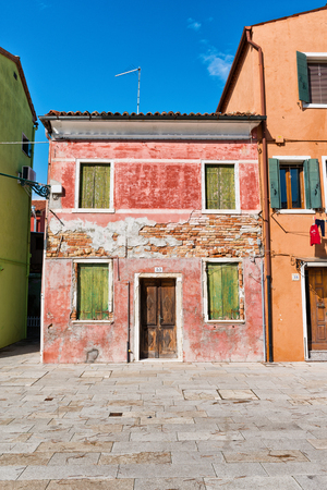 Urban decay on Burano, Venice, Italy with a view of the shuttered facade of an old red house with exposed brickwork, missing plaster and faded peeling paint