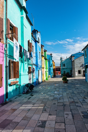 row of houses: Deserted Pedestrian Plaza Lined with Brightly Colored Row Houses in Residental Neighborhood on Sunny Day, Burano, Islands of Murano, Venice, Italy