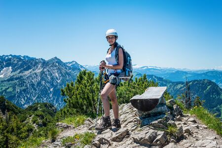 endeavor: Confident single female hiker standing on stones beside bench at mountain peak under clear blue sky with copy space Stock Photo