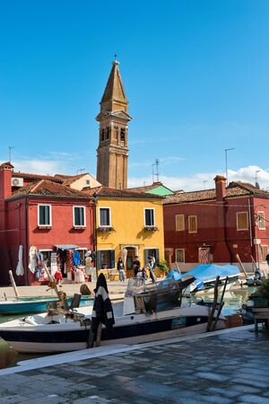 alongside: Boats and colorful houses on Burano, Venice, Italy with tourists walking alongside the canal and the leaning campanile of San Martino behind