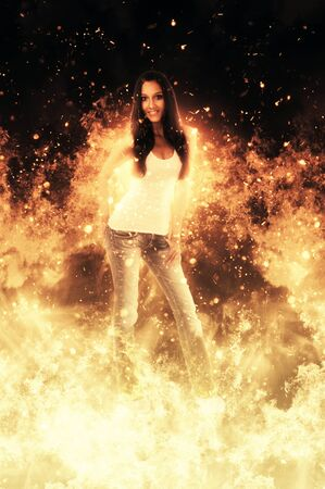 incendiary: Attractive slender smiling woman standing in amongst fiery hot yellow orange flames with shooting sparks engulfing her in a conceptual image