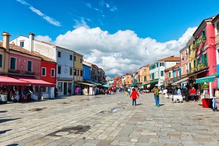 Busy shopping street in famous Burano with its colorful houses near Venice, Italy
