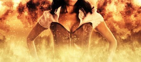 engulfed: Sexy woman in a bustier engulfed in burning orange flames in a conceptual close up view of her upper torso standing with her hands on her hips Stock Photo
