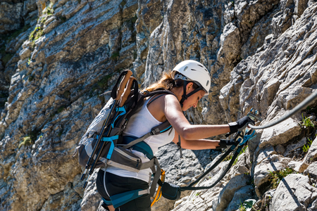 cliff face: Fit athletic woman mountaineering climbing a steep rocky cliff face with the aid of ropes on a sunny summer day
