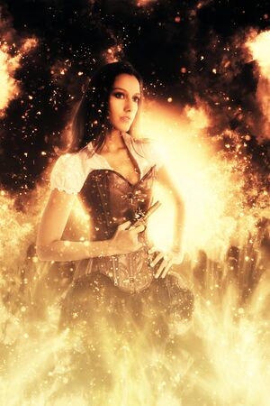incendiary: Retro young woman wearing a sexy bustier standing with her hand on her hips holding a gun engulfed in flames and fiery sparks looking to the right of the frame in a conceptual image