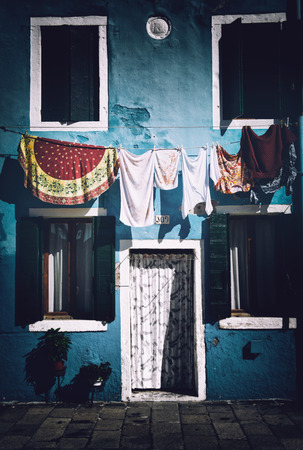 single family home: Freshly Washed Laundry Hanging to Dry on Elevated Clothesline in front of Blue Facade of Single Family Home on Sunny Day on Island of Burano, Venice, Italy