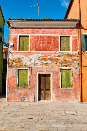 Old weatherworn house on Burano, Venice with exposed brickwork and faded paint and closed shuttered windows