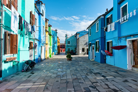 traditional house: Pedestrian walkway with colorful houses and washing drying in the sun, Burano, Venice, Italy, a popular tourist attraction Editorial