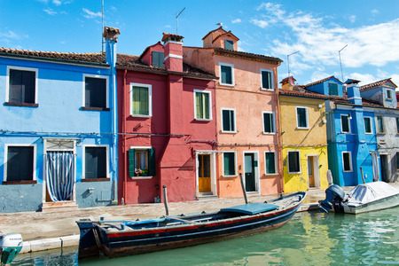 destination scenic: Boats moored in front of colorful houses, Burano, Venice, Italy in a scenic view of this popular tourist destination Editorial