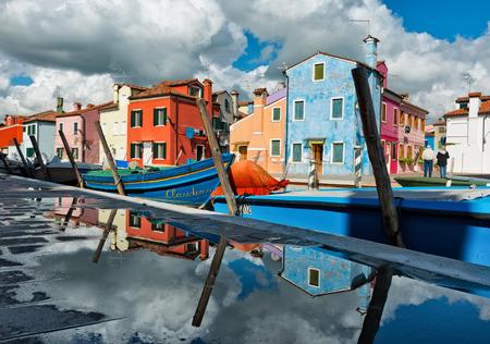 case colorate: Riflessioni di case colorate a Burano, Venezia, Italia in una pozza d'acqua sul marciapiede lungo il canale con le sue barche ormeggiate