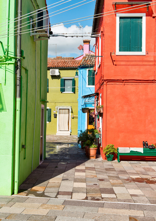enclave: Colorful enclave of brightly painted houses, Burano, Venice, Italy leading, off a paved courtyard with flowerpots