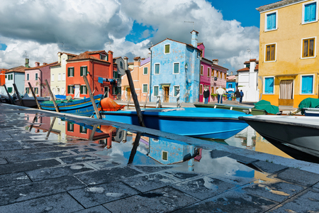 alongside: Colorful houses and architecture, Burano, Venice, Italy reflected in a pool of water on the walkway alongside the canal with moored boats under a cloudy blue sky
