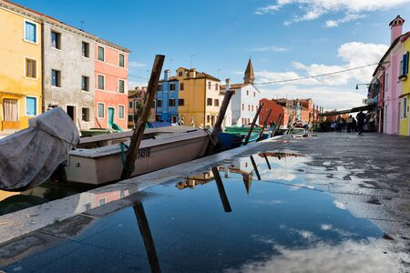 Reflections in a puddle on Burano, Venice, Italy with a boat moored in the canal in front of brightly colored fishing houses on a sunny day Editorial