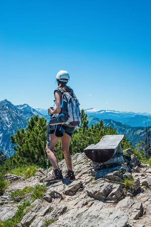 endeavor: Single female hiker near bench at mountain summit with beautiful clear blue sky and copy space above her