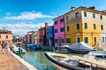 Scenic landscape view of a canal on Burano, Venice Italy with its brightly colored houses and boats moored on the water on a sunny day
