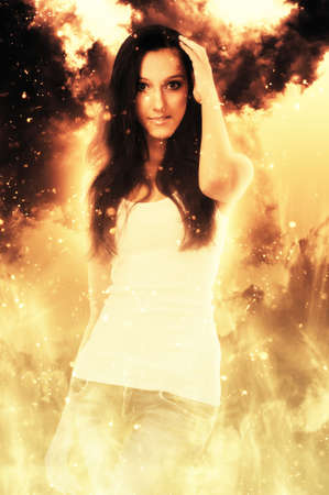 evocative: Beautiful grinning woman in white shirt holding hand near top of head while surrounded by flames Stock Photo
