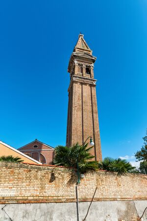 The famous leaning campanile of San Martino on the island of Burano, Venice, Italy, a popular tourist attraction